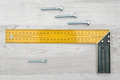 A yellow angle ruler and four metal bolts horizontally placed on white wood background. Royalty Free Stock Photo
