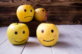 yellow apples with drawn emotions