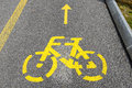 Yellow arrows and bicycle sign of a cycling path Royalty Free Stock Photo