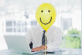 Yellow balloon with happy face hiding businessmans face Royalty Free Stock Photo