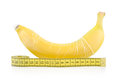 Yellow banana with condom and measuring tape isolated on white background Royalty Free Stock Photos