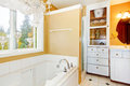 Yellow bathroom with white storage combination and elegant chandelier.
