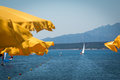 Yellow Beach Umbrellas in Line Near Shoreline and White Sailboat Royalty Free Stock Photo