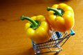 Yellow bell peppers in trolley on wood board Stock Photo