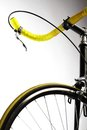Yellow bicycle detail on a handlebar and wheel of a Stock Images