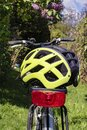 Yellow bike helmet lying on the luggage rack of a bicycle Royalty Free Stock Photo