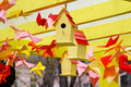 Yellow birdhouses and colorful origami birds Royalty Free Stock Photo