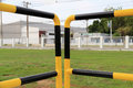 Yellow and black iron fence around small groundwater pump Royalty Free Stock Photo