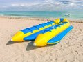 Yellow and blue banana boat lays on the beach Stock Photos