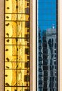 Yellow and blue reflections on facade glass of high rise building Royalty Free Stock Photo