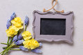 Yellow and blue spring flowers and empty frame on grey textu