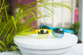Yellow and blue sunglasses on white terrace over blurred pink house background. Royalty Free Stock Photo