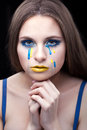 Yellow blue tears of the girl close up portrait a with makeup and and Stock Photos