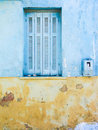Yellow and blue wall with window a ruined of a building in greece a closed by light shutters Stock Images