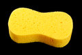 Yellow body care sponge isolated on the black background Royalty Free Stock Photo