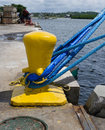 Yellow bollard with blue ropes Stock Photography