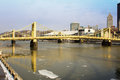 Yellow bridges across the allegheny painted iron suspension cross icey river toward downtown pittsburgh pennsylvania Royalty Free Stock Image