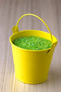 Yellow bucket with a green sea salt Stock Images