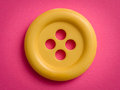 Yellow button on pink paper Royalty Free Stock Photography