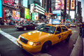 Yellow cab on Times Square traffic and animated LED signs, is a symbol of New York City and the United States, May 12, 2016 Royalty Free Stock Photo