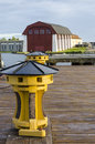 "Yellow capstan karlskrona old used to heave down sailing ships during th and th centurys in the background ""the wasa shed"" a Royalty Free Stock Photo"