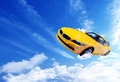 Yellow car flying over the clouds Royalty Free Stock Photos