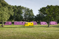 Yellow caravan amongst pink caravans colored parked on grass one and five Royalty Free Stock Photos