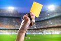 Yellow card hand of referee with and whistle in the soccer stadium Stock Photos