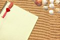 Yellow checkered notepad in sand with bookmark background with space for text or image Stock Photos