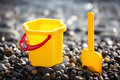 Yellow children's bucket with scoop on seacoast Royalty Free Stock Photos