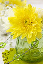 Yellow chrysanthemum in a glass vase on white wooden background Royalty Free Stock Photography