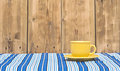 Yellow coffee cup and saucer on a colorful tablecloth Stock Photo