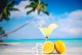 Yellow cold drink on a beach with lemon and ice Royalty Free Stock Photo