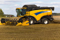 Yellow combine harvester on a wheat field with blue sky Royalty Free Stock Photo