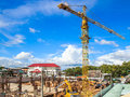 Yellow crane in a construction site building tower Royalty Free Stock Image