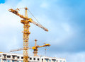 Yellow cranes work in modern houses massive concrete living under construction Stock Images