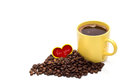 Yellow cup of coffee with coffee beans and small red heart isolated on white background Royalty Free Stock Photo