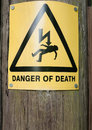 Yellow danger of death sign on wooden post