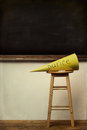 Yellow dunce hat on stool with chalkboard Royalty Free Stock Photos