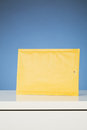 Yellow envelope a paper mail on a white desktop with a blue background vertical image Stock Image