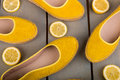 Yellow espadrilles shoes near slices of lemon on wooden background. Top view.
