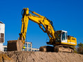 Yellow excavator digging earth construction site Royalty Free Stock Images