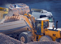 Yellow excavator loads big gravel Royalty Free Stock Images