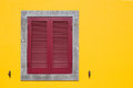 Yellow facade with a window with red shutter Royalty Free Stock Photo