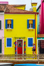 A yellow fisherman house in burano venice girl dressed as gondoliere walks front of Royalty Free Stock Photography