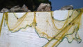 Yellow fishing net drying on the wall Royalty Free Stock Photo