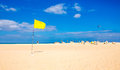 Yellow flag on the beach Royalty Free Stock Photo