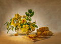 Yellow flowers and a cake still life with Stock Images