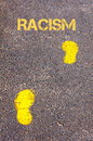 Yellow footsteps on sidewalk towards racism message conceptual image Royalty Free Stock Image