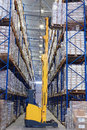 Yellow forklift raises palletising on top shelf of the rack. Royalty Free Stock Photo